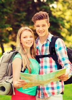 smiling couple with map and backpack in forest