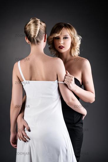 Elegantly dressed blondes hugging at camera