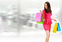 Young woman with bags in shopping mall.