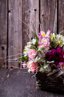 Pink bouquet from gillyflowers and alstroemeria in the basket on old wooden background