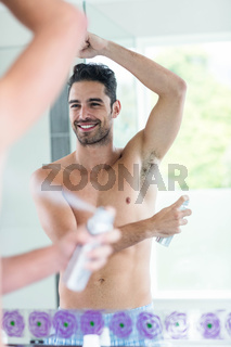 Handsome man using spray deodorant