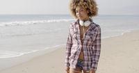 Girl With Headphones Walking On The Beach