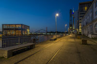 Harbor road in the Media Harbour with historical crane overlooking the Rhine Tower in the blue hour