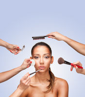Portrait of young female surrounded by hands with beauty tools