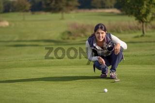 Golferin liest ein Grün vor dem Putten