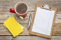 blank paper on clipboard and tea