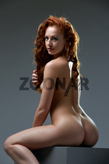 Curly red-haired woman posing nude at camera