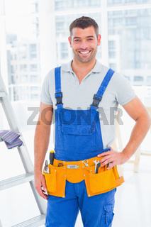 Handyman in overalls at modern office