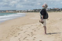 One Senior standing on the beach holding his face in the sun