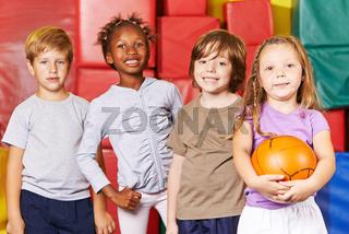 Kinder Team mit Ball in Turnhalle