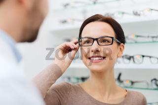 woman choosing glasses at optics store