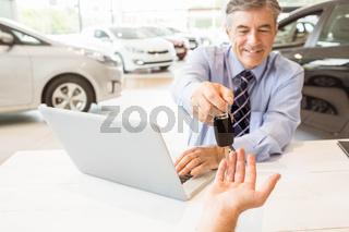 Smiling salesman holding a customer car key