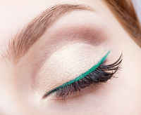 female face makeup with closed eye and green eyeliner