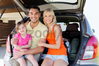 happy family with hatchback car at home parking
