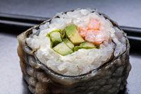 Macro Maki sushi served on black background.