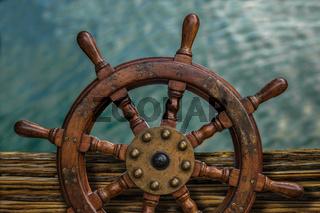 Ships Wheel Against Ocean Water