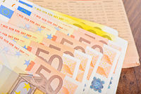 Close-up of Euro banknotes with newspaper