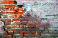 Red brick wall half covered with concrete, frame for design. Half painted wall. Concrete cracked wall grunge background