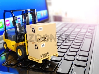 Concept of delivering, shipping or logistics. Forklift on laptop keyboard.