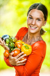 young woman in red blouse with tomatoes, eggplants, peppers