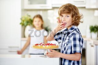 Junge nascht am Geburtstag vom frischen Obstkuchen