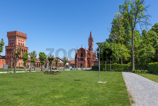 Green lawn, church and medieval tower in Pollenzo, Italy.