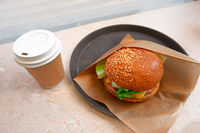 Hamburger in paper and takeaway coffee cup. Hot drink cup and tasty burger. Small breakfast in cafe