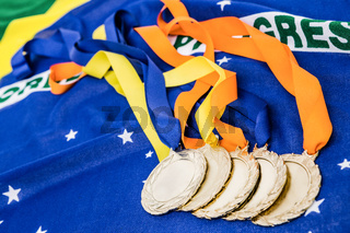 Close-up of gold medals on brazilian flag