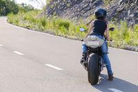 Blonde girl rides on modern motorcycle.
