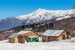 Rural houses and snowy mountains in Piedmont, Italy.