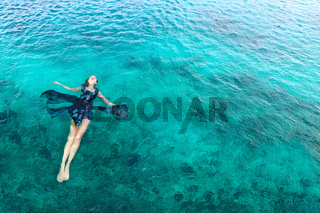 Woman in dress relaxing lying on the water