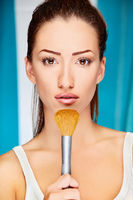young woman holding powder brush