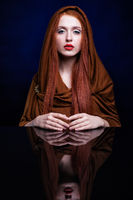 Young woman with ginger hair and scarf over reflection mirror on blue background