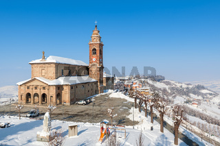 Parish church and snowy hills in Italy.