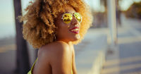 Smiling Girl with Afro Resting on Promenade
