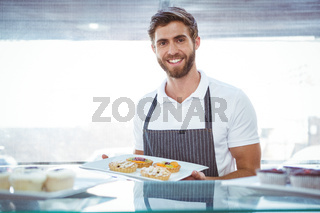 Smiling worker holding pastry behind the counter