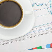 Coffee cup over financial charts