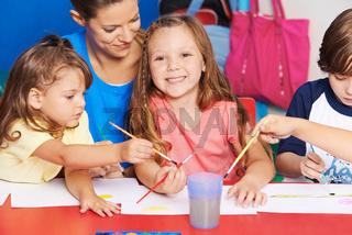 Lehrerin und Kinder malen in Vorschule