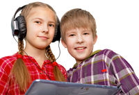 Family Fun: Brother and sister listening music on tablet PC