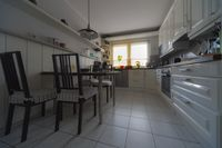 Interior view of a white kitchen with table and 4 chairs