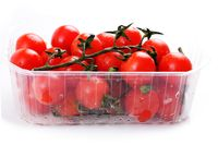 Cherry tomatoes in a plastic basket on a white