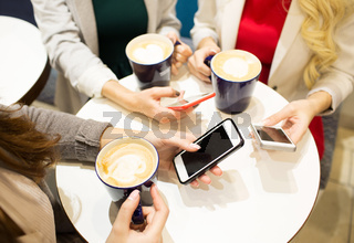 close up of hands with coffee cups and smartphones