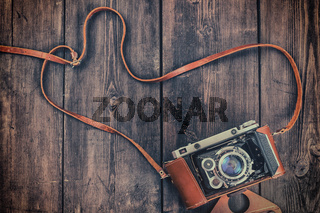 Old retro vintage camera on grunge wooden background