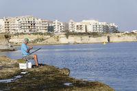 Fisherman in front of Marsalforn, Gozo, Malta