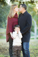 Mix Race Couple Kissing As Young Son Hides His Eyes