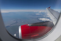 Looking out the window of an airplane as it passes the French coast of the Bay of Biscay.