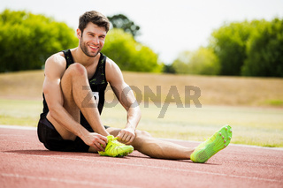 Athlete tying his shoe laces on running track