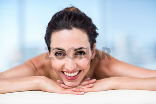 Smiling brunette relaxing on massage table