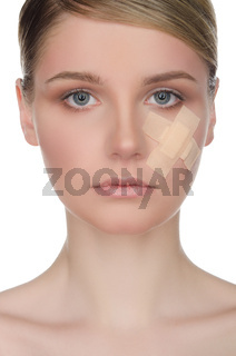 Young woman with medical plaster on her face