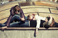 Group of teenage school girls lying on sidewalk